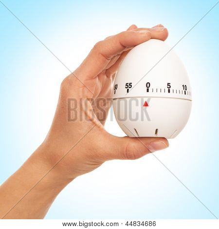 Kitchen timer in woman's hand over background