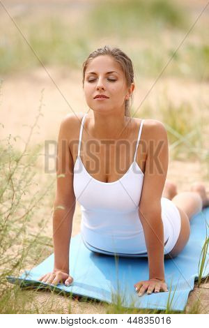 Beautiful caucasian woman making yoga at the beach near sea