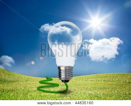 Transparent light bulb floating in a green field with a green cord