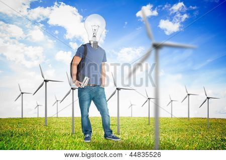 Male student with a light bulb head in the middle of sunny wind turbine field
