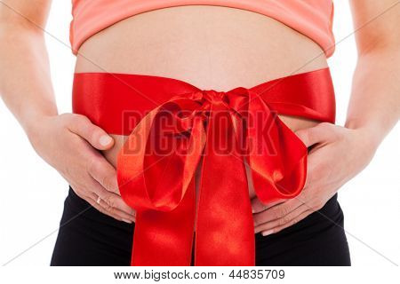 Beautiful pregnant belly with bow on a white background