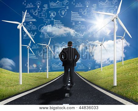 Businessman standing in middle of road with wind turbines either side looking at graphs on the horizon