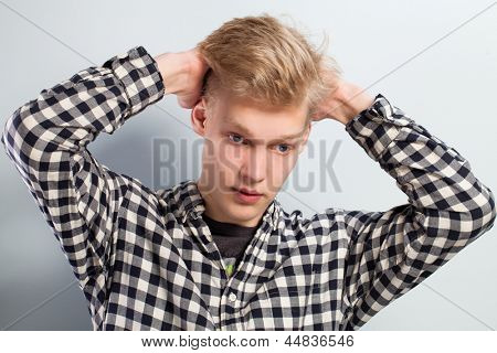 Young handsome guy with hand on head over grey background