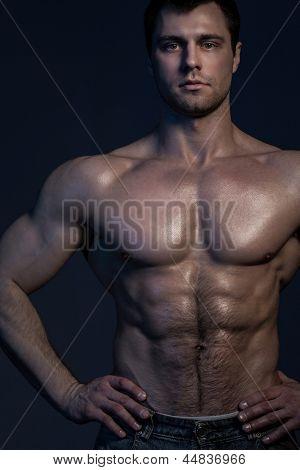 Closeup portrait of handsome muscular guy on dark background