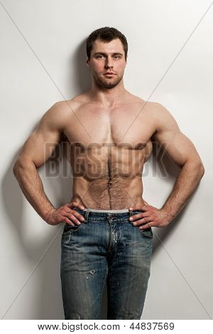 Handsome muscular guy with naked torso isolater over a grey background