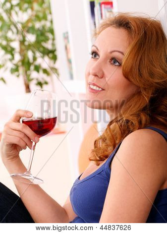 Middleaged happy woman enjoy glass of red wine at home