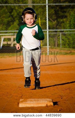 Young child running bases while playing baseball