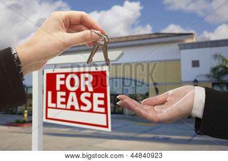 Real Estate Agent Handing Over the Keys in Front of Vacant Business Office and For Lease Sign.