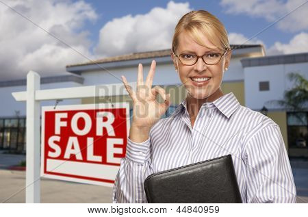 Smiling Businesswoman with Okay Sign In Front of Vacant Office Building and For Sale Real Estate Sign.