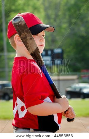 Portrait of child preparing to bat during organized league baseball game