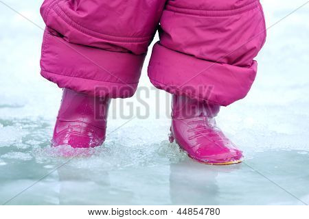 Child gumboots in a puddle