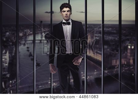 Elegant man over evening city background