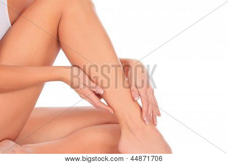 Woman sitting on the floor touches leg by hand, white background