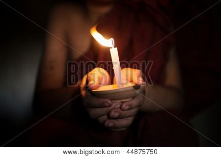 Little monk holding a candlelight