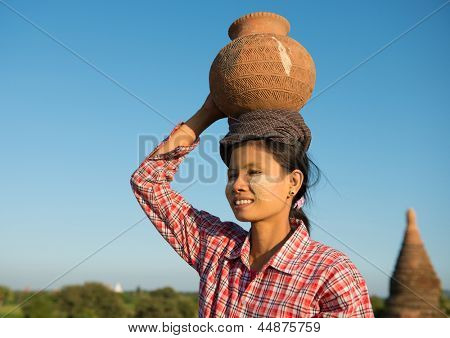 Portrait of Asian traditional female farmer carrying clay pot on head going back home, Bagan, Myanmar