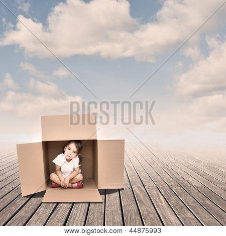 Menina dentro de uma caixa em um píer