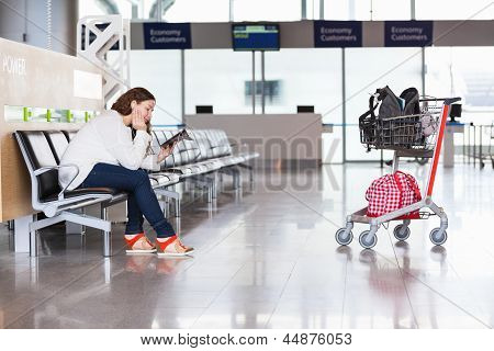 Tired Woman Waiting Flight In Airport Lounge With Luggage Hand-cart