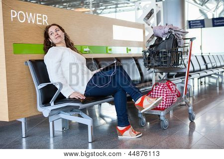 Transit Passenger Spending Time With Tablet Pc In Airport Lounge With Luggage Hand-cart