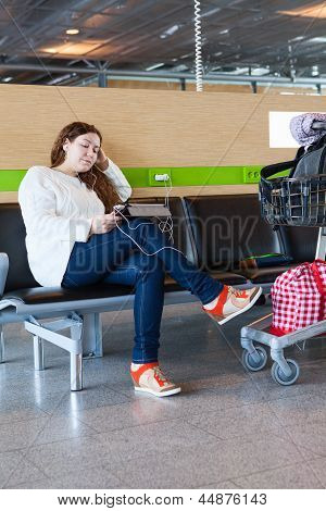 Tired Woman Looking At Tablet Pc In Airport Lounge With Luggage Hand-cart
