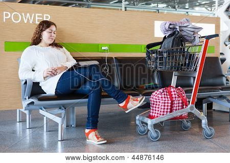 Tired Woman Charging Tablet Pc In Airport Lounge With Luggage Hand-cart