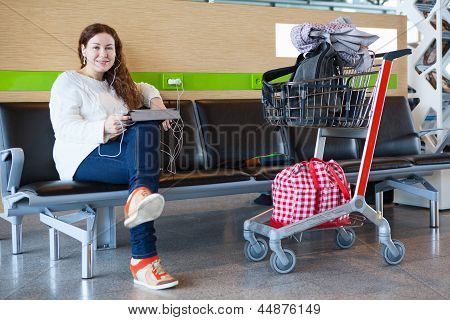 Happy Young Caucasian Woman Sitting With Luggage Hand-cart In Airport Lounge