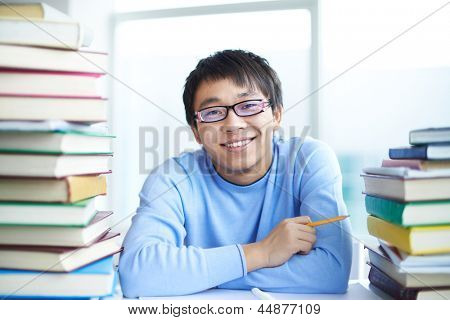 Portrait of successful Asian student surrounded by books looking at camera