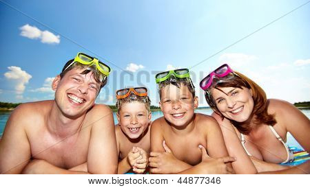 Photo of happy family looking at camera during summer recreation