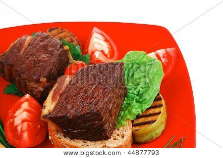 bbq : beef (pork) steak garnished with apples , fresh tomatoes, hot pepper, chives and lettuce, on bread, over red plate isolated on white background