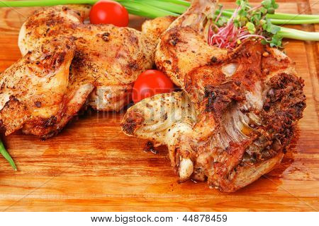 grilled meat : chicken quarters garnished with green sprouts and red peppers on wooden plate isolated over white background