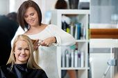 stock photo of beauty parlor  - Mirror reflection of hairdresser giving a haircut to woman at parlor - JPG