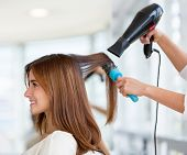 stock photo of blowing  - Beautiful woman at the hairdresser blow drying her hair - JPG