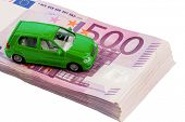 green model car on banknotes, symbolic photo for car buying, financing and costs