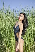 stock photo of one piece swimsuit  - Beautiful young woman in exotic tropical location wearing one - JPG