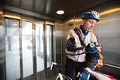 pic of elevators  - Young male cyclist with courier delivery bag using mobile phone in an elevator - JPG