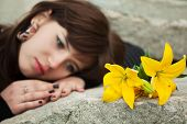 stock photo of headstones  - Young woman with a flowers lying on the tombstone - JPG