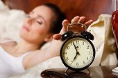 stock photo of sleepy  - Young sleeping woman and alarm clock in the bedroom - JPG