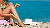 stock photo of suntanning  - Woman Applying Sunscreen Lotion on Her Sexy Legs at Beach - JPG