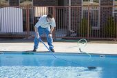 image of cleaning service  - Service man cleaning pool filters removing leaves that have fallen in pool this fall - JPG