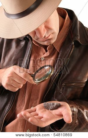 Adventurer geologist examines stone with magnifier