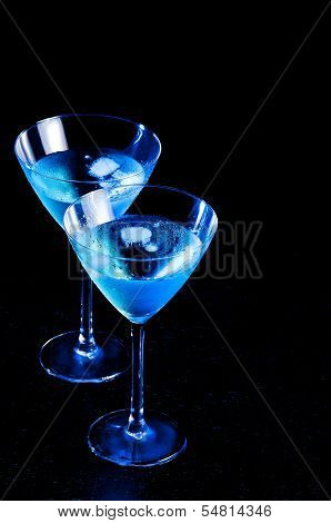 Two Glasses Of Fresh Blue Cocktail With Ice On Wood Table