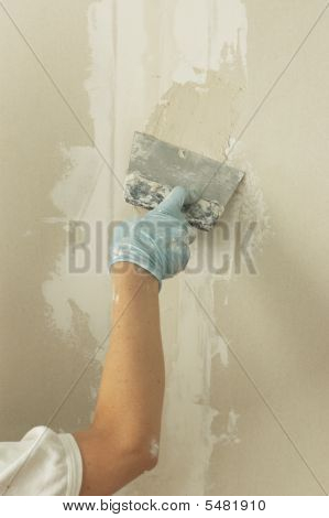 Woman Hand With Palette Knife Glazing Wall