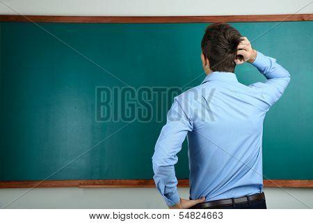 Young teacher near chalkboard in school classroom