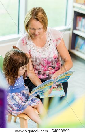 Mature teacher with schoolgirl reading book in library