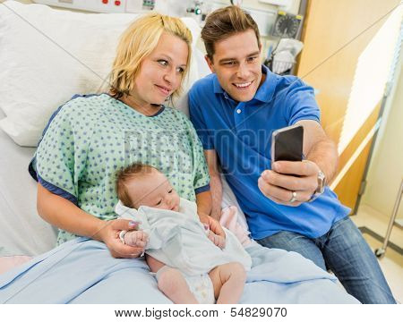 Mid adult man with woman and newborn babygirl taking selfportrait through mobile phone in hospital room