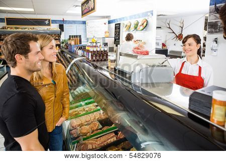Smiling young saleswoman attending customers at butcher's shop