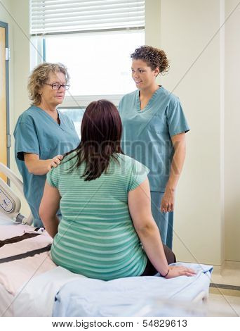 Female nurses and pregnant woman communicating in hospital room