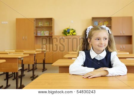 Little girl in school uniform sits at school desk and looks away in classroom in first grade for her alone.