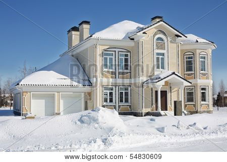 Two-storey light cottage with garage at frosty and sunny winter day.