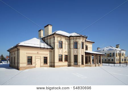 Simple two-storey new cottage with many windows on sunny frosty winter day.