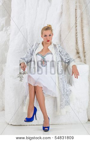 Beautiful girl in white dress and coat of Snow Maiden sitting in snow chair